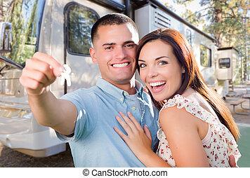 Una joven pareja militar con llaves frente a una nueva caravana