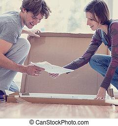 Una joven pareja mirando el manual de muebles de autoensamblaje