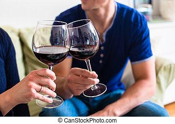 Una joven pareja romántica brindando con vino tinto mientras se sienta en él