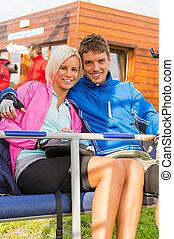 Una joven pareja sonriente sentada junto al ascensor