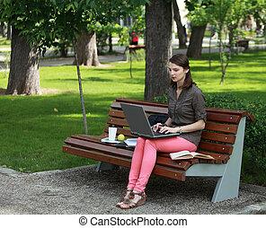 Una joven que estudia en un parque