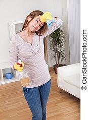 Una joven que limpia la casa