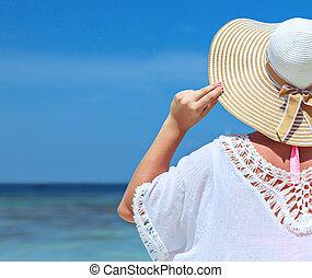 Una joven relajada mirando el océano tranquilo