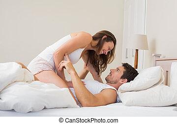 Una joven sentada sobre un hombre en la cama