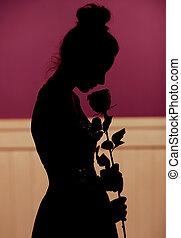 Una joven silueta sosteniendo flores