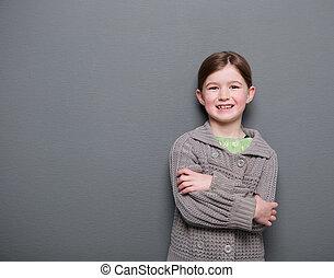 Una joven sonriendo con los brazos cruzados