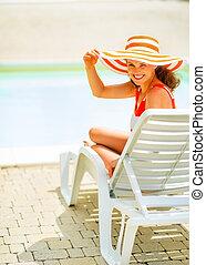 Una joven sonriente con sombrero sentado en una cama solar
