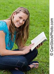 Una joven sonriente mirando la cámara mientras leía un libro