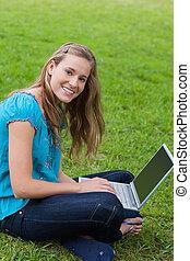 Una joven sonriente mirando la cámara mientras usa su portátil