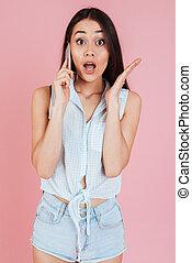 Una joven sorprendida hablando por teléfono