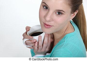 Una joven sosteniendo taza de café