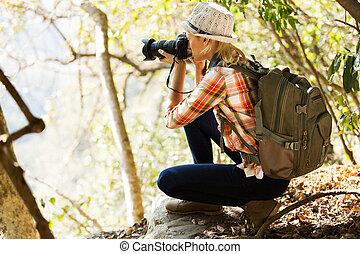 Una joven tomando fotos en el bosque