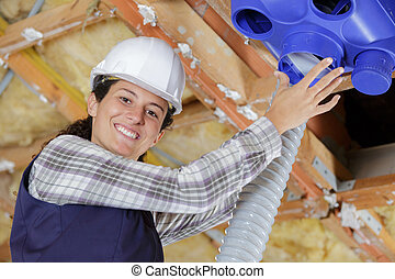 Una joven trabajadora instalando un sistema de ventilación en el techo