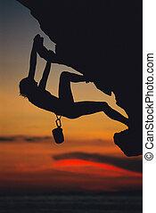 Una joven trepando una roca