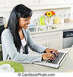 Una joven usando computadora en la cocina