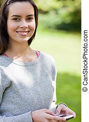 Una joven usando su celular mientras estaba en un parque mirando a la cámara