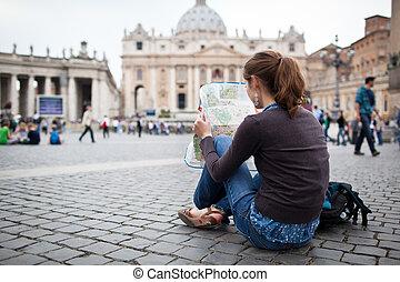 Una joven y bonita turista estudiando un mapa en la plaza de San Pedro en la Ciudad del Vaticano en Roma