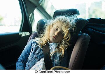 Una linda chica rubia durmiendo en un asiento de coche