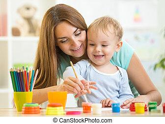 Una linda mujer jugando y pintando con un niño