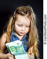 Una linda niña con dinero en la mano.