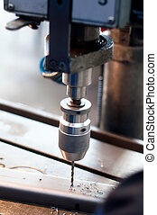 Una máquina industrial de CNC haciendo agujeros simétricos en una barra metálica