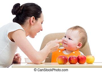 Una madre joven alimentando a su bebé