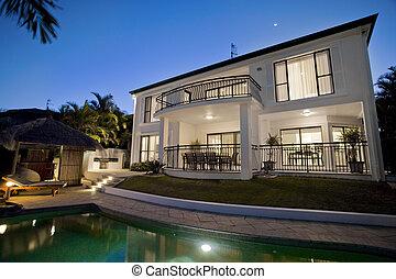 Una mansión lujosa al atardecer con vista a la piscina