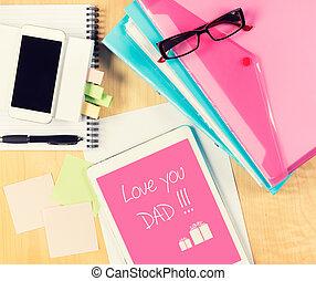 Una mesa de oficina desordenada con la tarjeta del día de los padres en una tableta digital. Vista desde arriba con espacio de copia