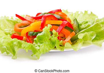 Una mezcla de verduras frescas de un páprika de color sobre hojas de ensalada verde en un fondo blanco