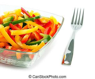 Una mezcla de verduras frescas de un paprika de color en una placa de vidrio en un fondo blanco con un enchufe