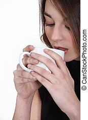 Una morena bebiendo café.