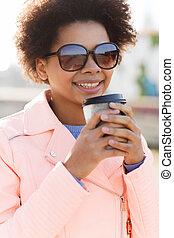 Una mujer afroamericana sonriente bebiendo café