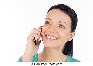 Una mujer al teléfono. Una joven alegre hablando por teléfono y sonriendo mientras está aislada en blanco