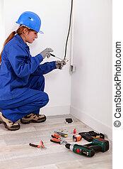 Una mujer arreglando la electricidad