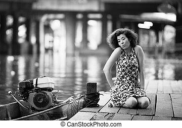 Una mujer asiática se sienta en un río de madera