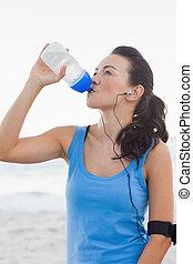 Una mujer bebiendo agua embotellada después de hacer deporte