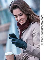 Una mujer bebiendo café con cara de celular en un día frío en una ciudad