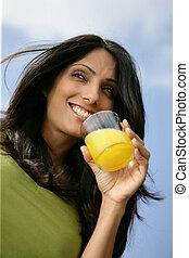 Una mujer bebiendo un vaso de jugo de naranja