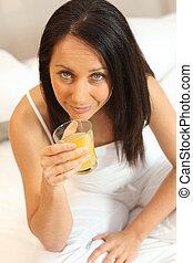 Una mujer bebiendo un vaso de jugo