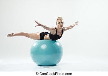 Una mujer caucásica haciendo ejercicio de pelota de fitness
