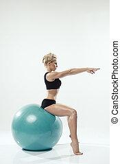 Una mujer caucásica haciendo ejercicio de pelota de fitness, sentado en la pelota