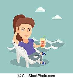 Una mujer caucásica relajándose en un chaise-longue.