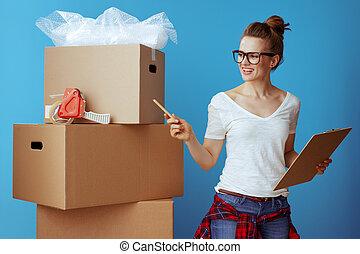 Una mujer cerca de una caja de cartón usando una lista móvil y cajas de recuento