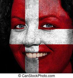 Una mujer con bandera pintada en la cara para mostrar apoyo a Austria