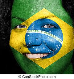Una mujer con bandera pintada en la cara para mostrar apoyo a Brasil