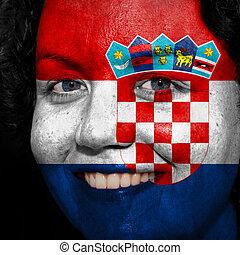 Una mujer con bandera pintada en la cara para mostrar apoyo a Croacia