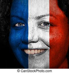 Una mujer con bandera pintada en la cara para mostrar apoyo a Francia