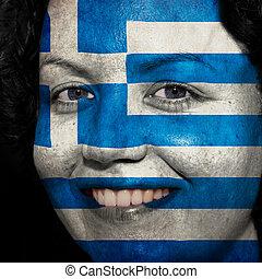 Una mujer con bandera pintada en la cara para mostrar apoyo a Grecia