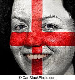 Una mujer con bandera pintada en la cara para mostrar apoyo a Inglaterra