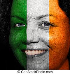 Una mujer con bandera pintada en la cara para mostrar apoyo a Irlanda